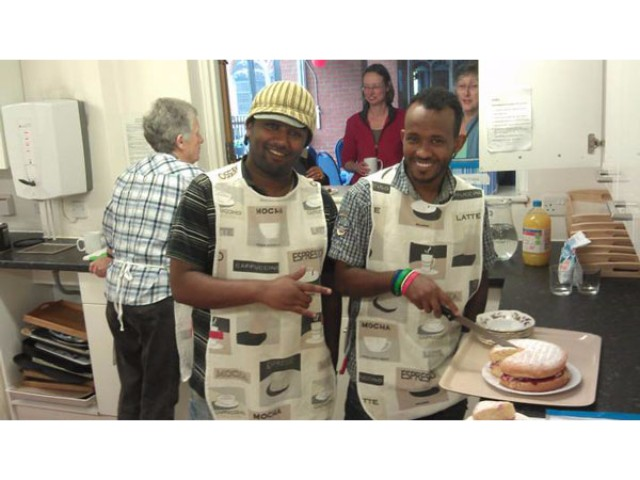 Asylum seekers helping out in the kitchen as volunteers at a drop in centre